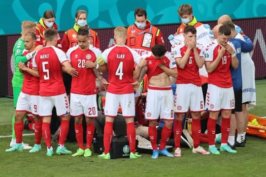 Denmark players form a human screen around Christian Eriksen during Finland clasbh