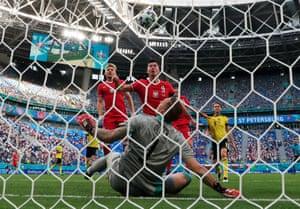 Poland's Robert Lewandowski and Sweden's keeper Robin Olsen watch the ball the ball clattered off the bar.