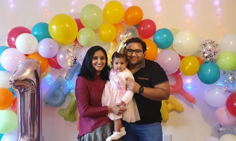 Shubhi, Anaisha and her dad standing in front of a balloon arch to celebrate her daughter's firts birthday.
