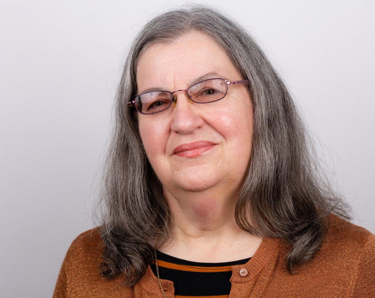 Headshot of Sarah Beeson. She has grey hair, is wearing glasses and a brown cardigan