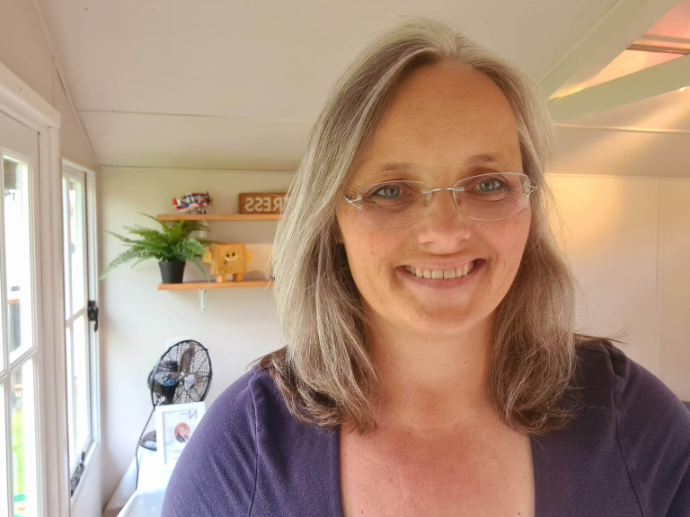 Claire Steed. She has grey hair, is wearing glasses and a purple top.