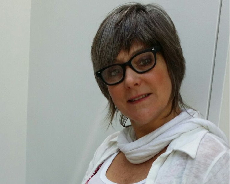 Alison Bruce - she has short brown hair, wears glasses and has a white top and scarf on