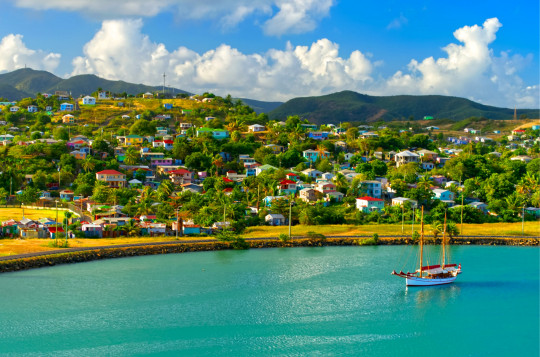 Colourful image of a single sailboat moored in St John`s Harbour, Antigua with colourful Caribbean homes on the surrounding hills.