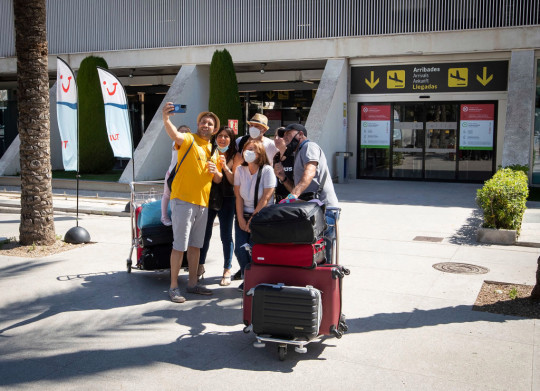 A group of tourists take a photo outside an airport