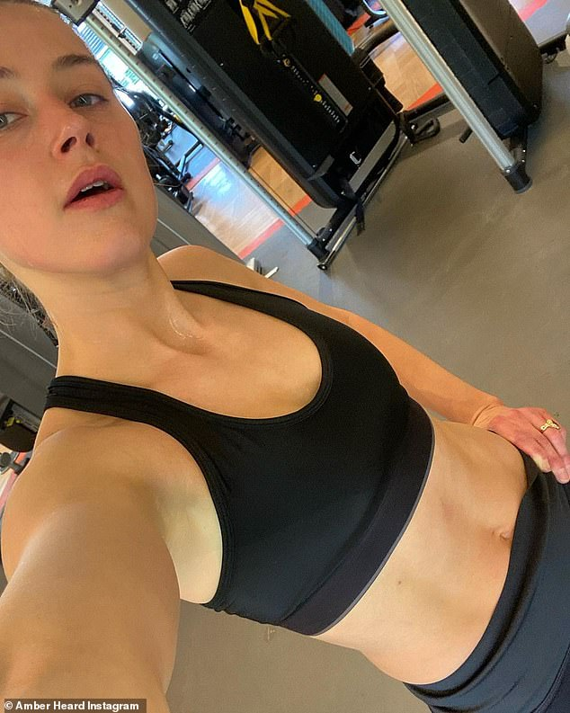 Working hard: Just a day prior, the Texas-born actress took to Instagram to share two selfies after having completed a gruelling workout. In the above snap, Amber showed off her washboard stomach in a black crop top and leggings while in the gym