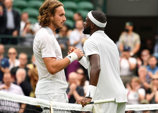 US player Frances Tiafoe (R) greets Greece's Stefanos Tsitsipas after winning their men's singles first round match on the first day of the 2021 Wimbledon Championships at The All England Tennis Club in Wimbledon, southwest London, on June 28, 2021.
