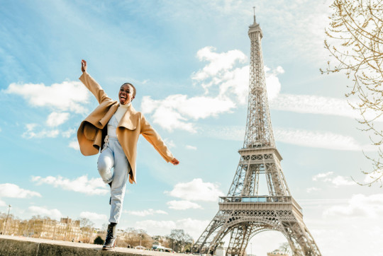 Excited woman jumping from retaining wall with Eiffel Tower in background, Paris, France