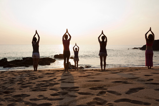 Women practicing yoga on beach at sunset