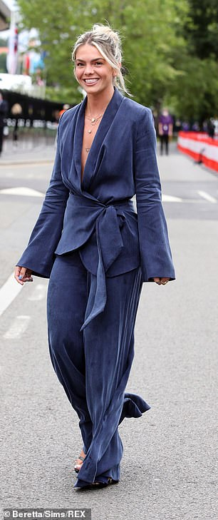 In blue: Louisa, 23, strutted into the grounds in a wrap around, low-cut, loosely-tied top and matching baggy pants