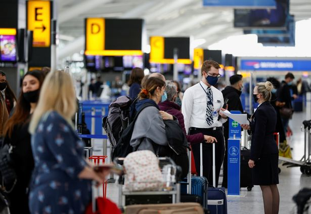 British Airways staff talk to each other as passengers stand in a queue to check-in desks