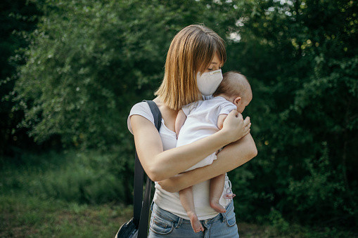 A mum wearing a facemask and standing outside holding her baby