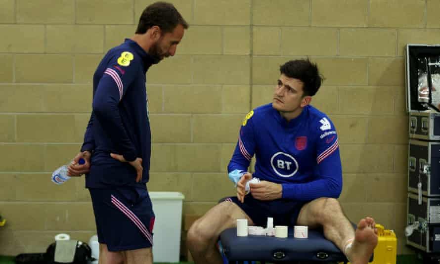 Harry Maguire gets treatment for his ankle injury as Gareth Southgate watches on.