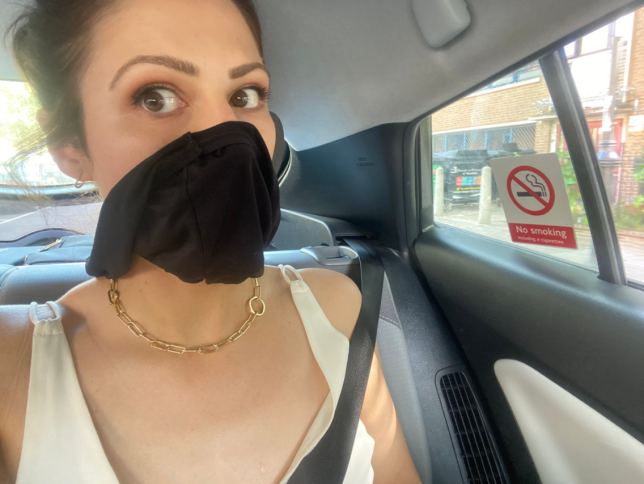 Nicola Thorp in a cab wearing black knickers on her face after forgetting her face mask