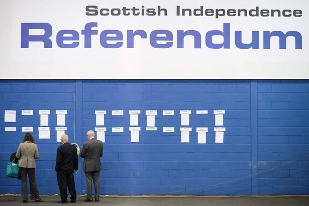People next to a referendum painting