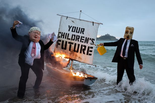 A boat burns at sunrise on Saturday, May 5, in front of St Michael's Mount with 'Your Children's Future' painted on the sail, as part of a 'theatrical action' by Ocean Rebellion ahead of the G7 summit.
