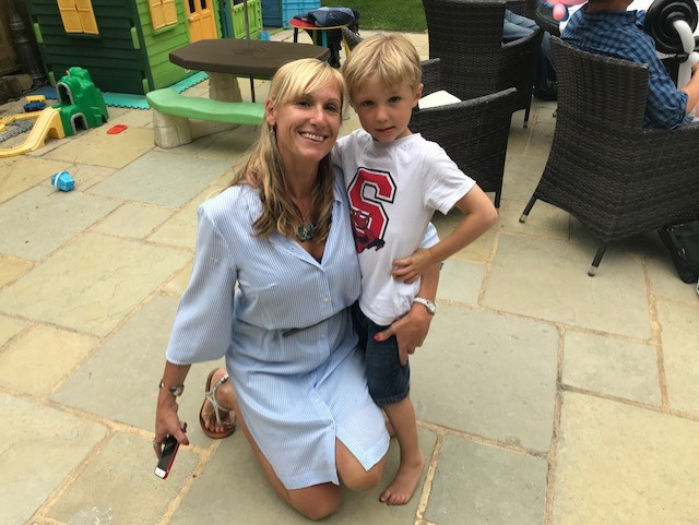 Sarah kneels beside her son James who's got his arm around his mum