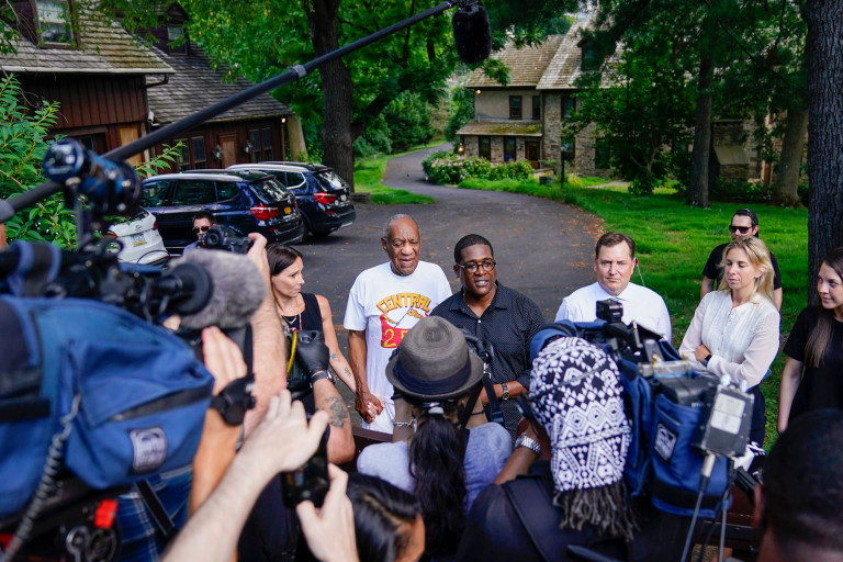 Bill Cosby, center, and spokesperson Andrew Wyatt, right, approach members of the media gathered outside the home of the entertainer