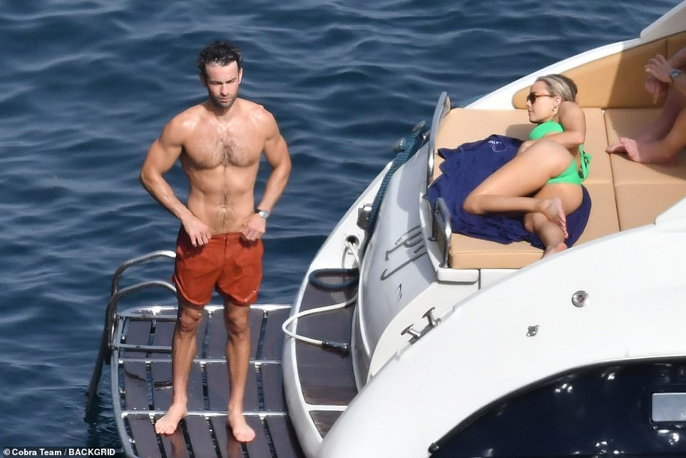 Chilled: Chace cooled off on the boat's platform, while a relaxed Rebecca looked on