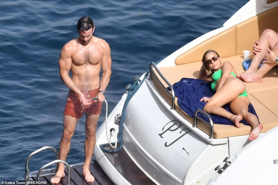 Flaunt: Rebecca stretched out on the boat's deck while Chace hosed himself down