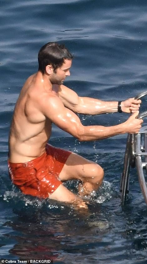 Taking a dip: Chace showed off his ripped abs and muscular arms as he climbed out of the water