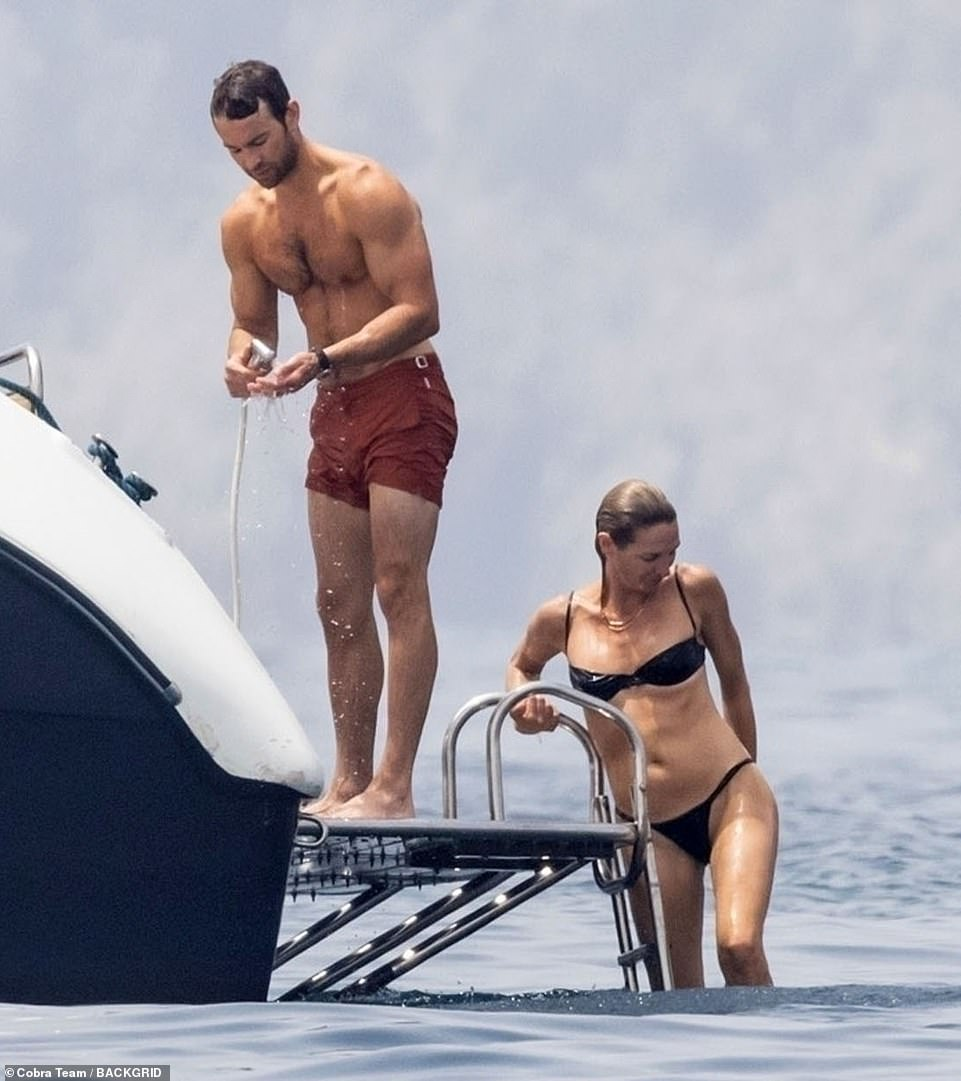 Group outing: A female pal in a black bikini was seen emerging from the water behind Chace