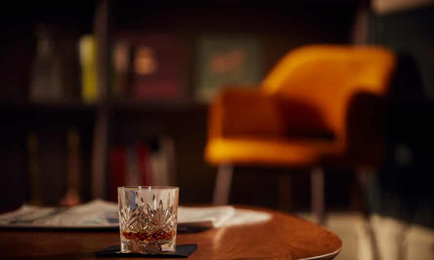 A glass of whisky on a table with an orange chair in the background