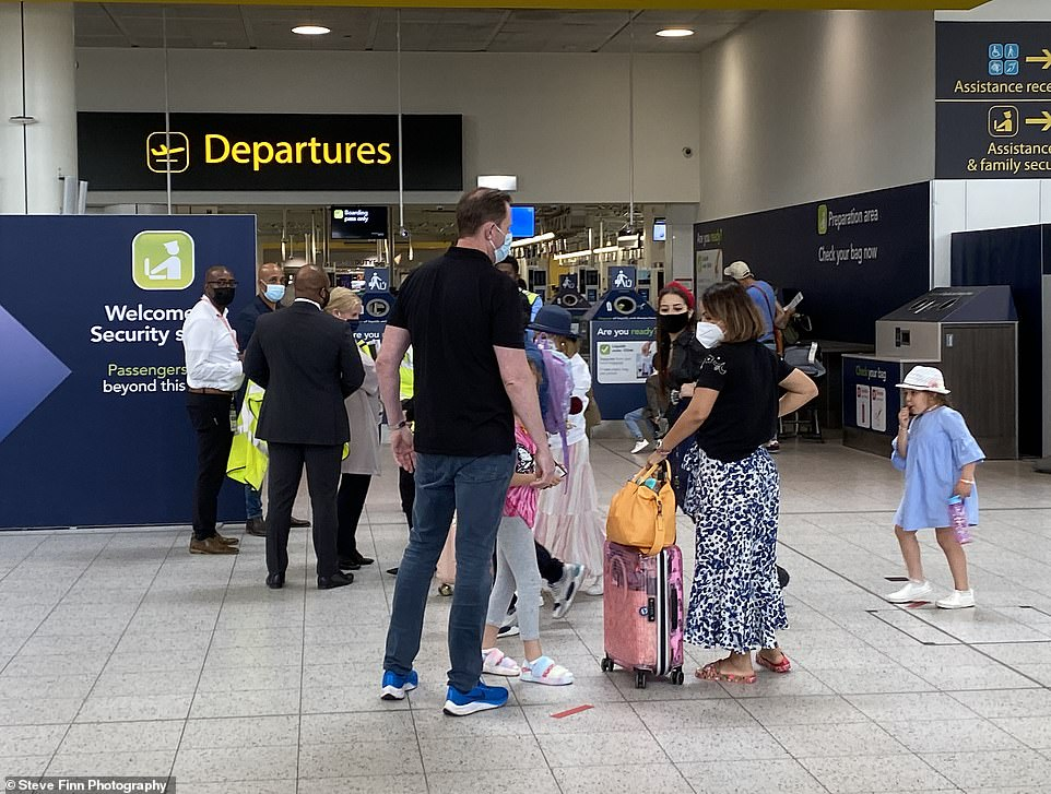 Summer holiday plans for thousands of Britons were left in tatters last night after the Balearic islands were axed from the 'green list' just a fortnight after they were approved for quarantine-free travel. Pictured: A family prepare to jet off from Gatwick Airport