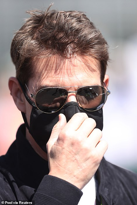 Safety first: Tom made sure he wore a black face mask while wandering round Silverstone