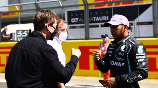 NORTHAMPTON, ENGLAND - JULY 18: Tom Cruise bumps fists with Lewis Hamilton of Great Britain and Mercedes GP on the grid before the F1 Grand Prix of Great Britain at Silverstone on July 18, 2021 in Northampton, England. (Photo by Bryn Lennon - Formula 1/Formula 1 via Getty Images)