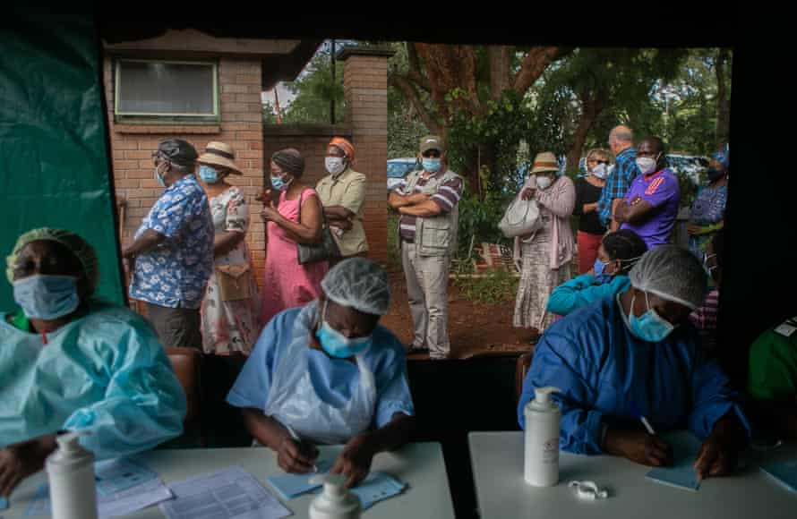 Older people queue while nurses conduct their duties