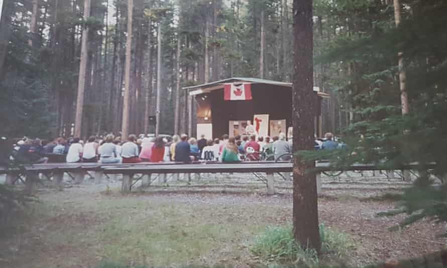 A park ranger gives a talk to a crowd in woods