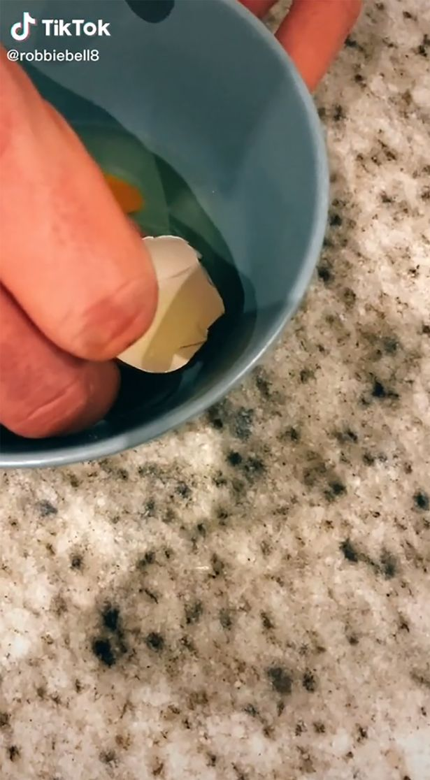 A bowl on a kitchen countertop. A hand holds an eggshell inside the bowl, which has scooped up a piece of broken eggshell.