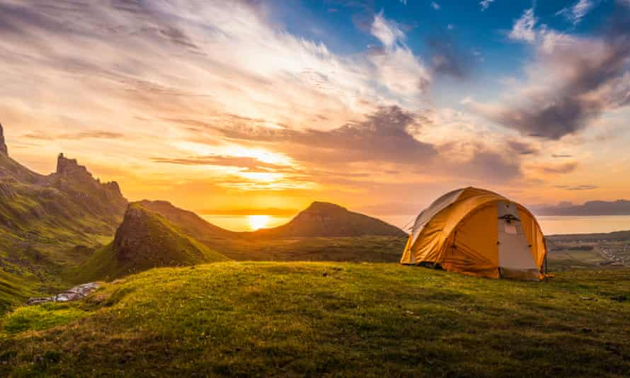 A tent in mountains in front of the setting sun.
