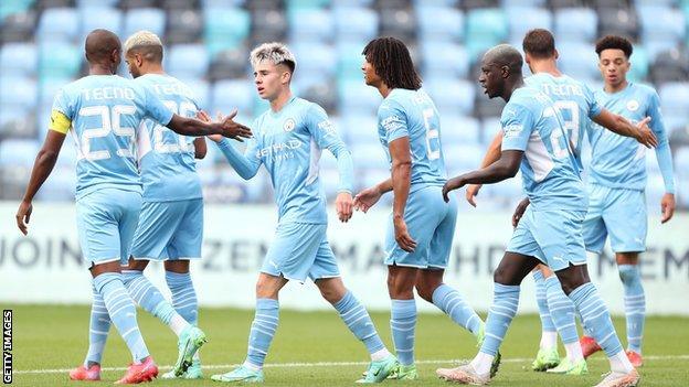 Man City celebrating a goal against Barnsley