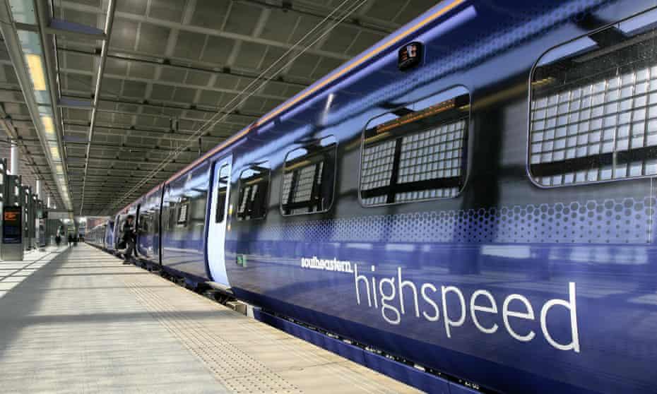 Shot down a platform of a rake of sleek modern dark blue carriages with paler doors, bearing the logo 'Southeastern highspeed'