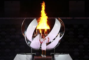 Naomi Osaka stands in front of the Olympic cauldron after the Olympic flame is lit.
