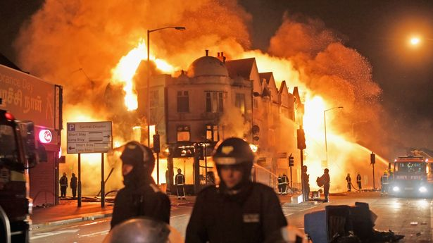Firefighters battle a large fire that broke out in shops and residential properties in Croydon, South London