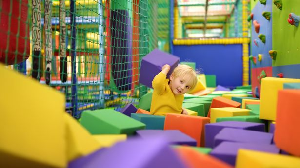 A child playing in a soft ballpit