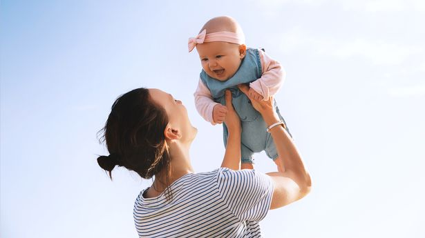 Young mother throws up baby in the sky, summer outdoors