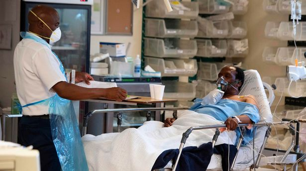 A hospital worker (L) and patient (R) with COVID-19 is seen in in the Resuscitation room of the COVID-19 ward at Khayelitsha Hospital, about 35km from the centre of Cape Town, on December 29, 2020