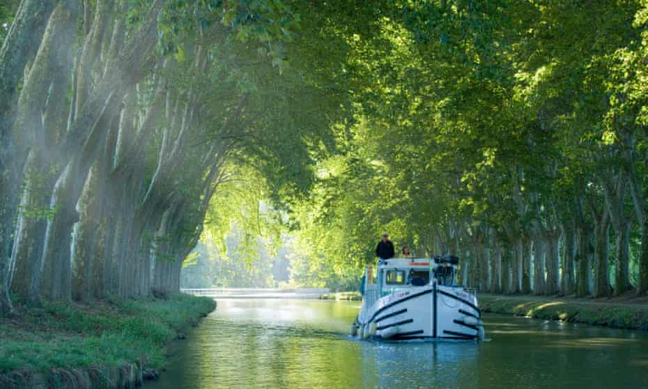 France, Languedoc, Carcassonne:  boat in tree lined canal
