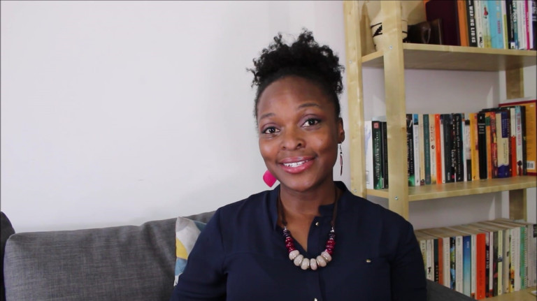 Tamara Bugembe, sitting on a sofa. She has her hair up and is wearing a dark shirt. There is a book case in the background.