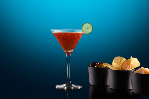 A cocktail glass filled with a red drink and a slice of lime on the side. Next to it are little pots of snacks like olives and crisps.