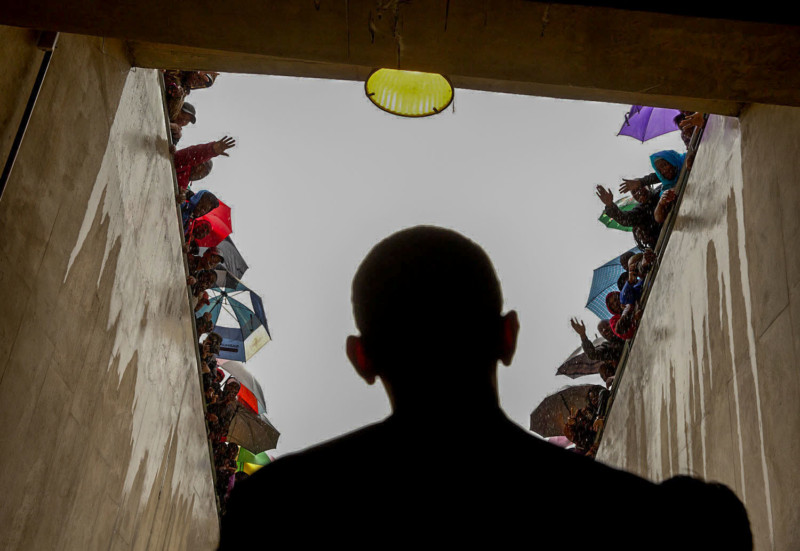 """Dec. 10, 2012 """"South Africans cheer as President Obama waits in a tunnel at the soccer stadium before taking the stage to speak at Nelson Mandela's memorial service. It was a long overnight flight to Johannesburg, a few hours on the ground in the pouring rain, and then a long flight back to Washington."""" (Official White House Photo by Pete Souza) This official White House photograph is being made available only for publication by news organizations and/or for personal use printing by the subject(s) of the photograph. The photograph may not be manipulated in any way and may not be used in commercial or political materials, advertisements, emails, products, promotions that in any way suggests approval or endorsement of the President, the First Family, or the White House."""