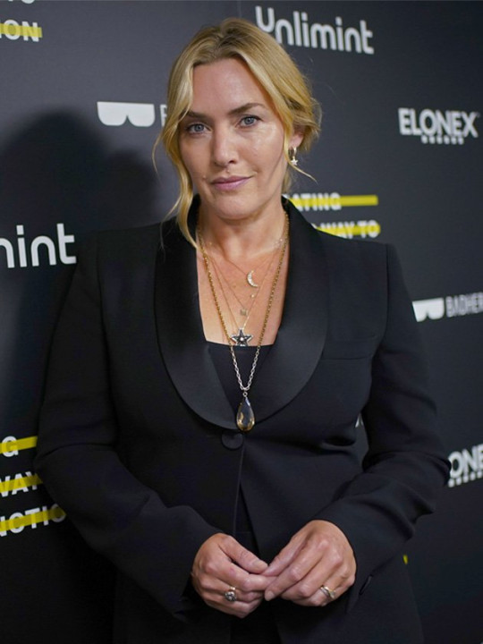 Kate Winslet looking at the camera wearing a black suit