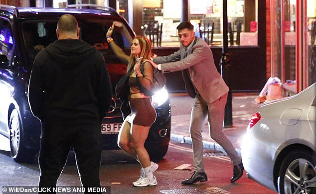 Walk this way: The man rested his hands on Maisie's shoulders as they crossed the road together in the busy clubbing district