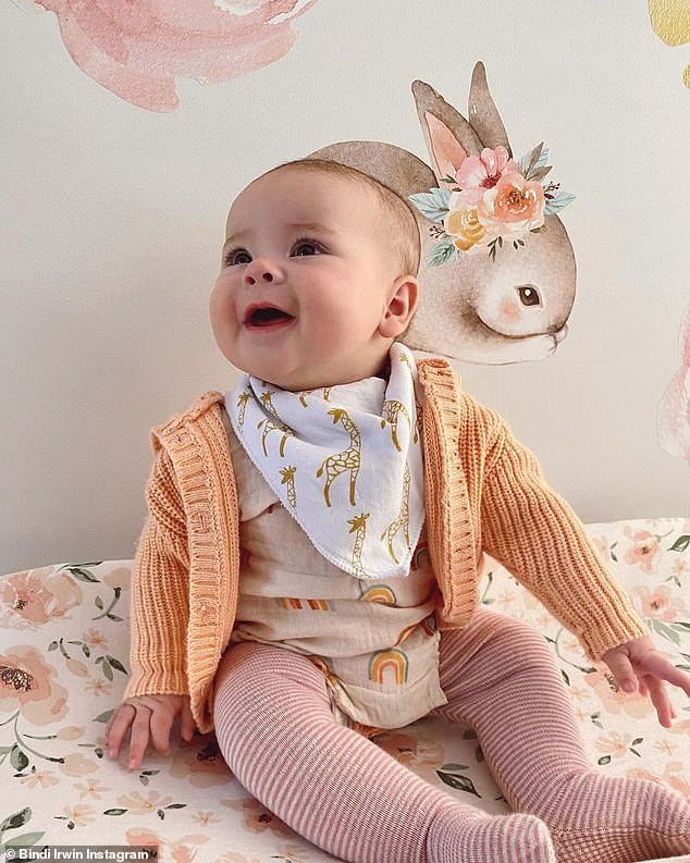 What a cutie!Bindi shared a new heart melting picture of baby Grace Warrior on Thursday.Little Grace was sitting up on her change table, dressed in a sweet colourful outfit, including striped leggings, a rainbow T-shirt, knitted cardigan and giraffe bib