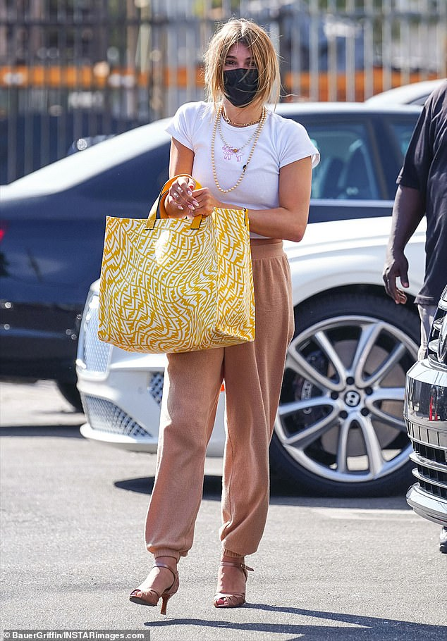 Sporty: On Thursday, her 21-year-old daughter Olivia Jade was seen entering the DWTS studio. She wore a white cropped T-shirt with beige sweatpants and matching open-toe heels
