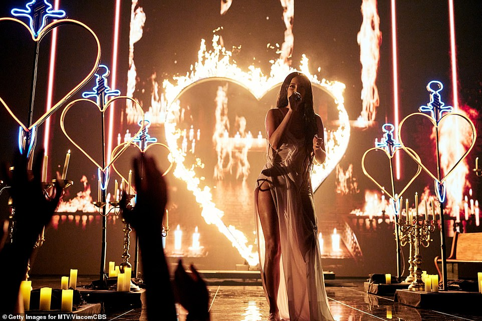 On fire: The stage design matched the intimate, somber nature of the song with several minimalist candle holders that bathed the dark set in amber light. Kacey wore her long raven locks, which were wet, down her front