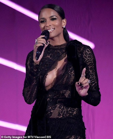 Sizzling:Ciara wasn't performing, but that didn't stop her from stealing the show when she walked out on stage in a stunning black lace dress that hugged her curves and featured a diagonal slit highlighting her cleavage